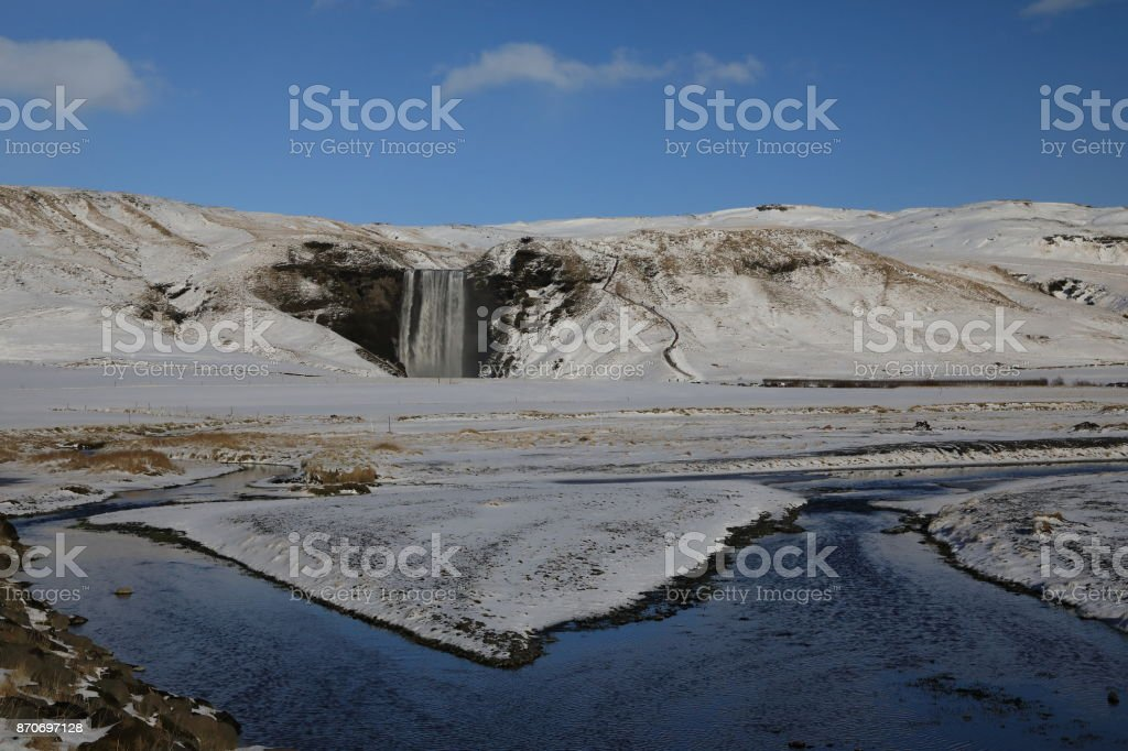 Iceland, Skogar, Skogafoss, Skogafoss waterfall surrounded by snow and ice in winter stock photo