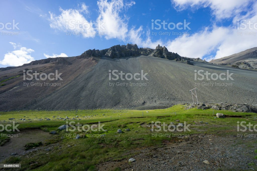 Iceland - Volcano with green meadow, blue sky and some clouds stock photo