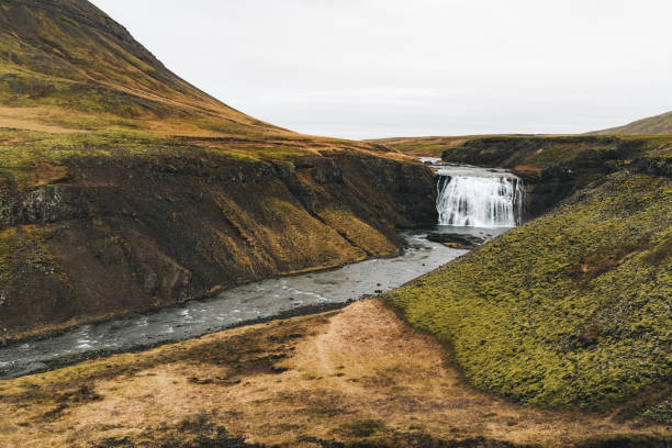 Iceland waterfall among green hills stock photo
