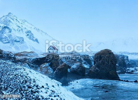 istock Iceland winter landscape with the solitary living house and cliffs near Arnarstapi village at dusk  during snowfall, Snaefellsnes, Iceland. 1051679500