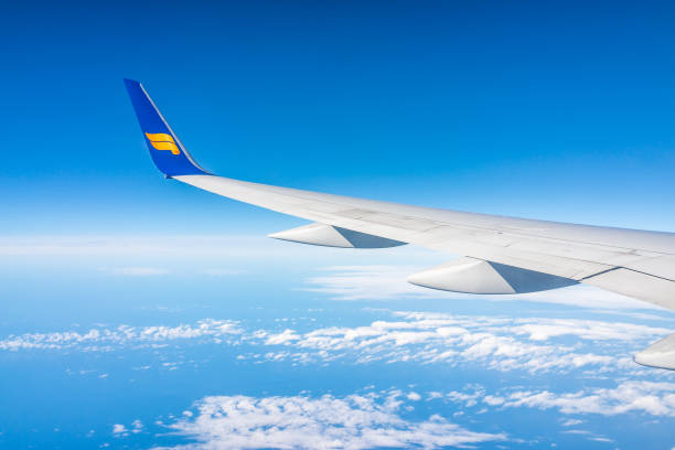 Icelandair blue airplane in sky with view from window high angle view over Atlantic Arctic ocean during sunny day, plane wing stock photo
