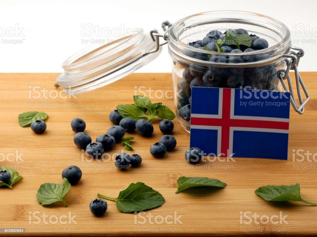 Bandeira da Islândia numa prancha de madeira com mirtilos isolado no branco - foto de acervo