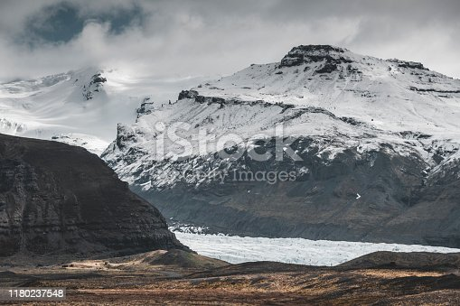 Icelandic landscape, snow-covered mountains, black volcanic rocks and storm clouds