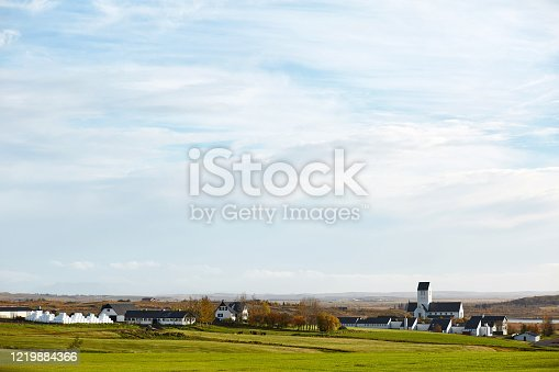 istock Icelandic landscapes. Beautiful countryside with church, farm houses, barns and cattle grazing at green pasture on clear blue sky background 1219884366