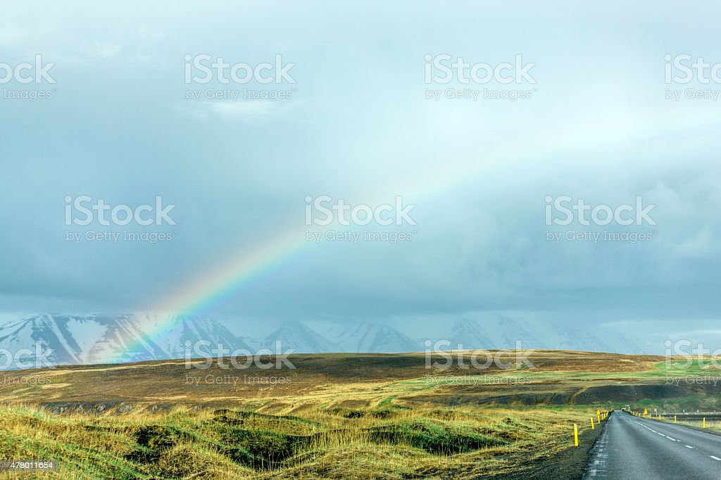 Icelandic road with snow-capped mountains and rainbow, snow markers stock photo