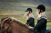 Icelandic girls, adorable young blonde-haired sisters, wearing matching traditional woolen sweaters, ride horses on their Fluguyri horse farm, Skagafjordur, Iceland, Europe