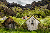 Icelandic turf houses and rocky canyon with waterfall in the background near Kalfafell village, South Iceland
