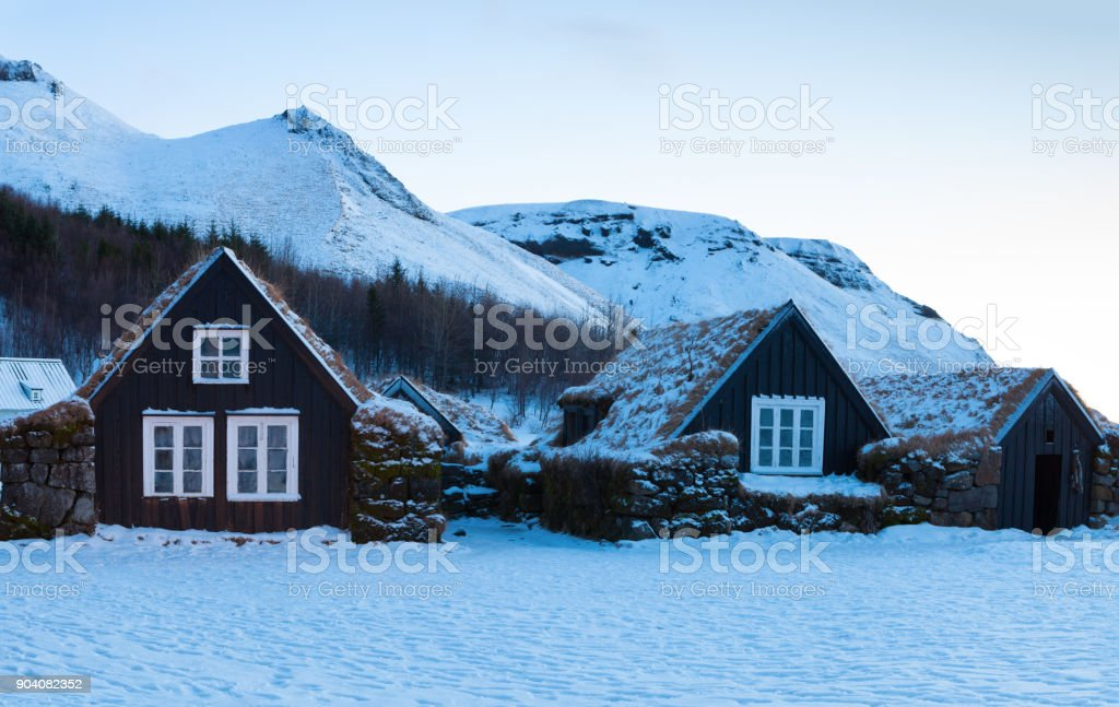 Icelandic turf houses at dawn in winter,  Skogar, Iceland. stock photo