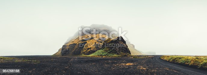 Panoramic view on remote rock Hjorleifshofdi rising from black sand at Myrdalssandur plain on the south coast of Iceland.