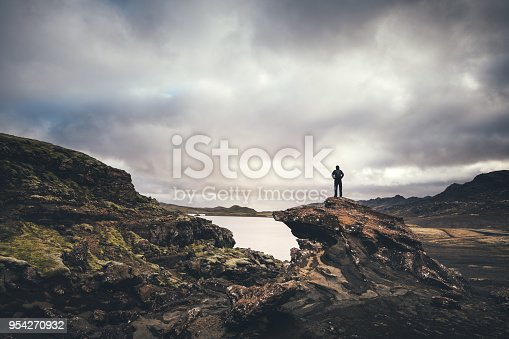 Man standing on the rock and enjoying the view on lake Kleifarvatn on the Reykjanes Peninsula in Iceland.