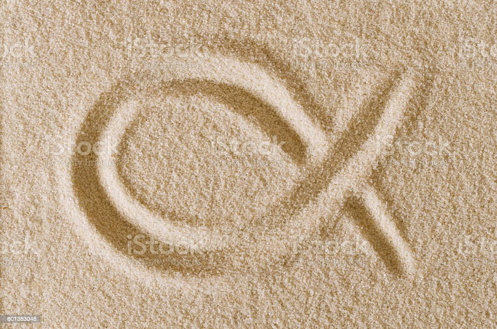 Ichthys, Jesus Fish symbol, drawn in sand macro photo stock photo