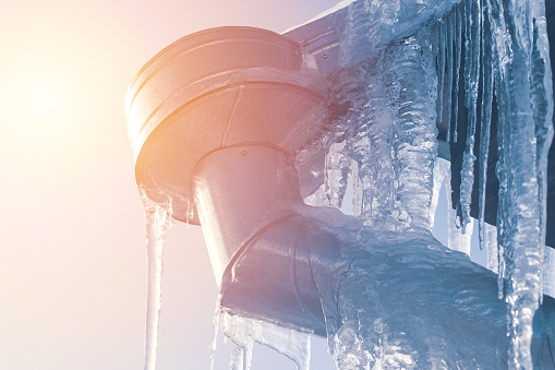 icicle cleaning from rooftop outdoors at sunny day. roof icicle problem concept.