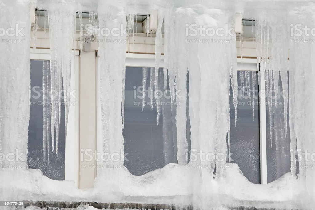 Icicle windows on winter time. Freeze temperatures backgrounds royalty-free stock photo