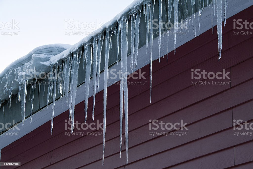 Icicles hang down from a building roof royalty-free stock photo
