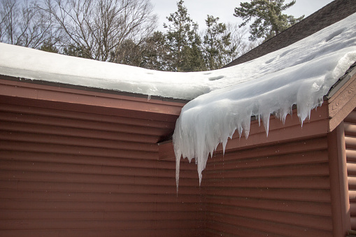 Icicles on a roof with water dripping from below on home exterior.