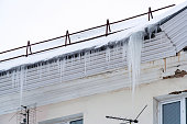 Icicles hang from the roof of the house. Early spring
