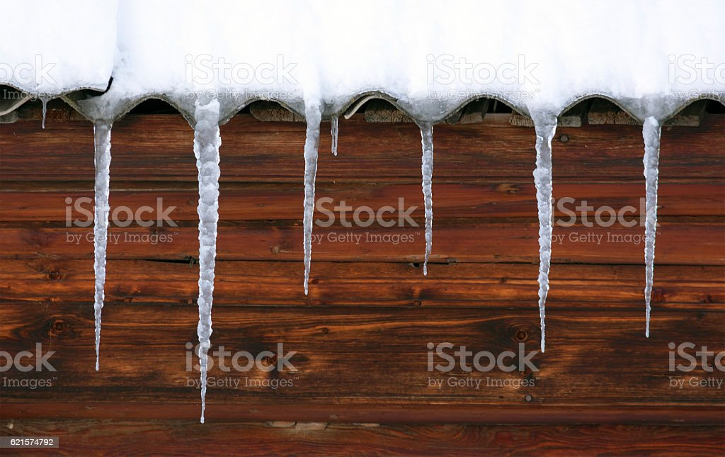 Icicles hang from the undulating roof. The wall of the photo libre de droits