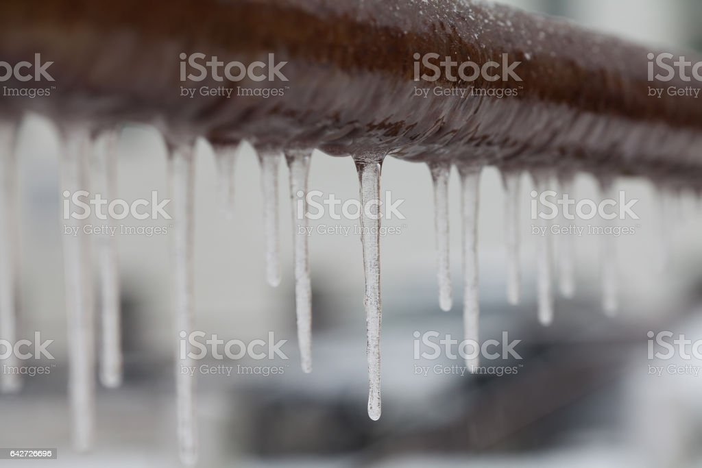 Icicles hanging from a brown pipe. Frozen water and metal surface, winter time concept. selective focus shallow depth of field stock photo