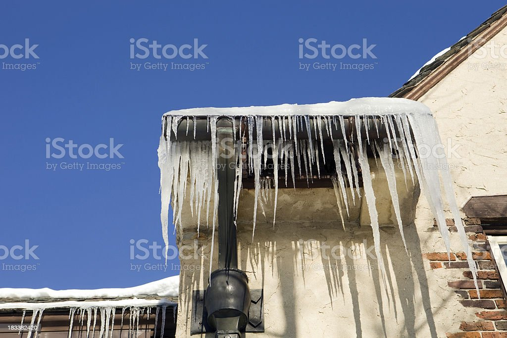 Icicles Hanging from a Mansion Roof against Clear Blue Sky royalty-free stock photo