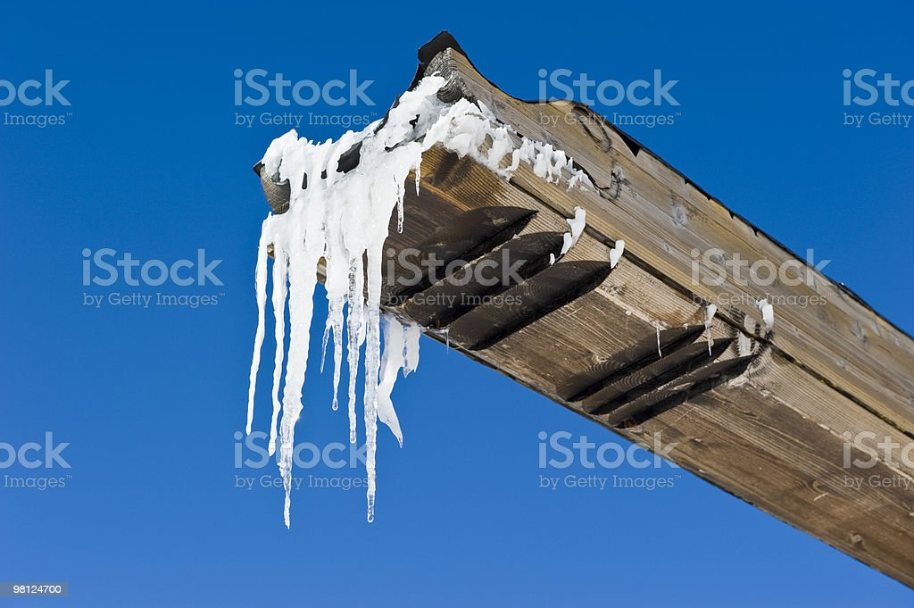 Icicles hanging from a Wooden outcrop royalty-free stock photo