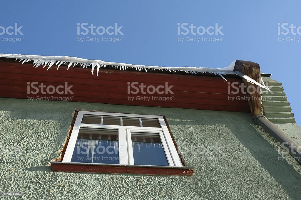 Icicles hanging from roof on green house royalty-free stock photo