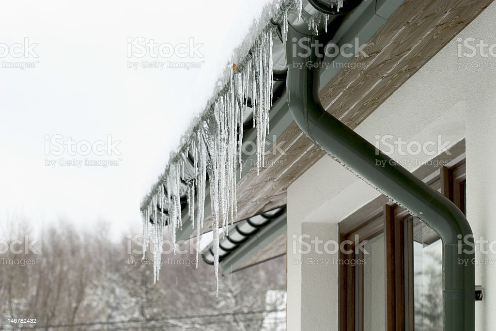 Icicles hanging from the roof of a house stock photo