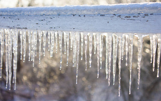 Icicles Hanging from Wood Fence stock photo