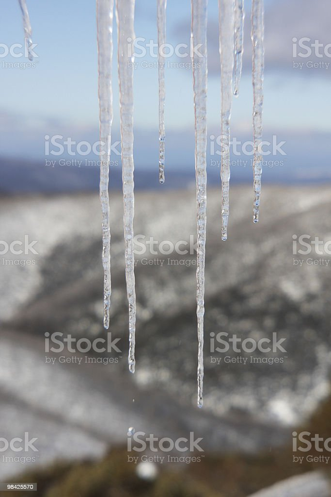 Icicles hanging with mountain in background royalty-free stock photo