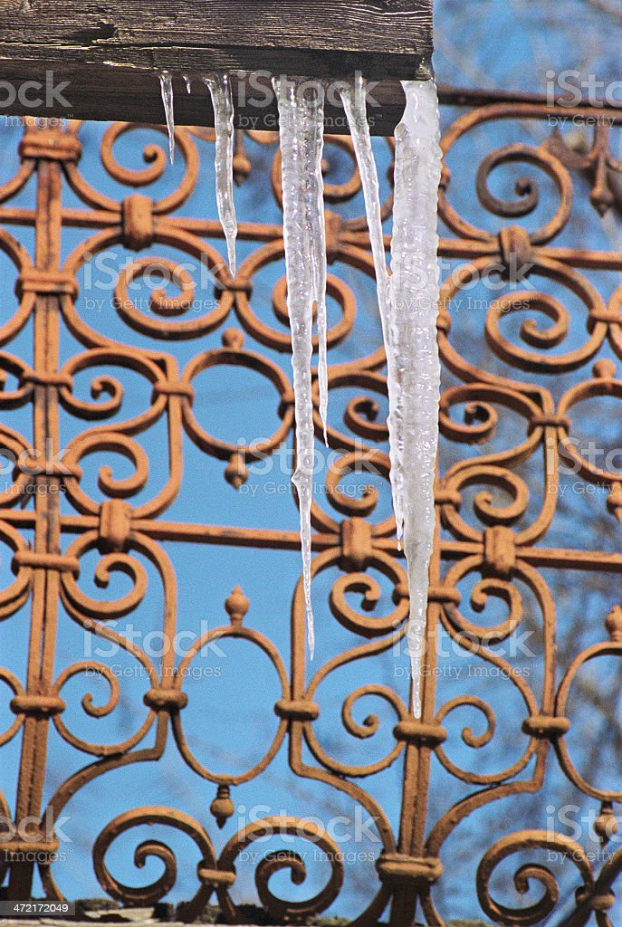 Icicles on a background of the old lattice. royalty-free stock photo