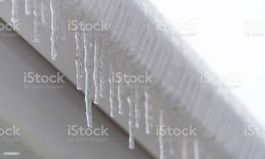 Icicles on gutter in freezing weather stock photo