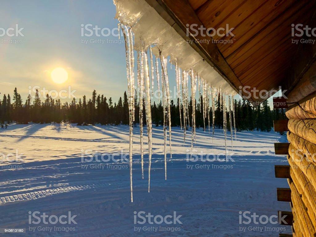 Eiszapfen an Dach und Sonnenuntergang – Foto