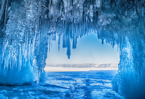 Baikal Lake in the winter cold day. Beautiful icy rocks with big ice crust.long icicles on the icy coastal cliffs of Olkhon Island
