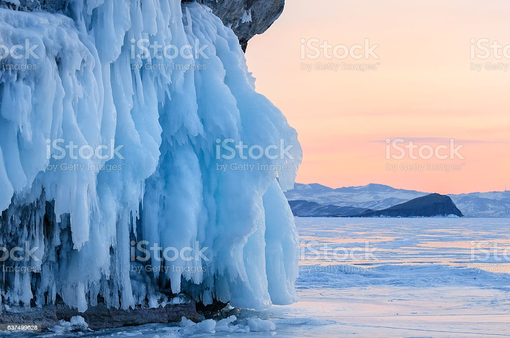 Icicles on the rocks on sunset, lake Baikal stock photo