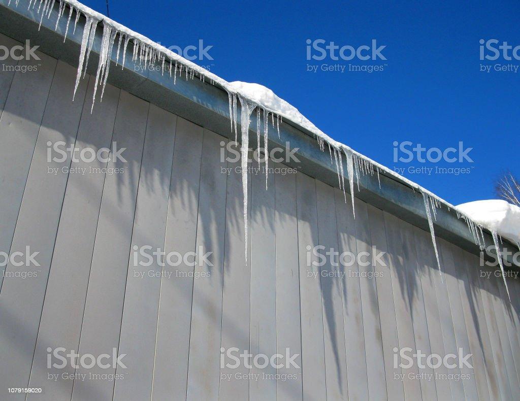 Eiszapfen auf dem Dach gegen den blauen Himmel – Foto