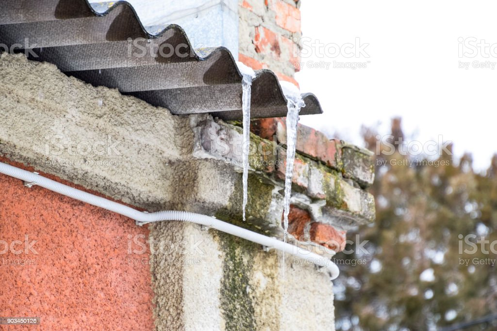Icicles on the roof. Insecure roof. Freezing water in the icicle. stock photo