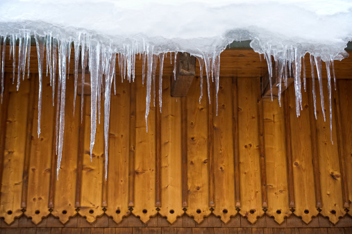 Many icicles hang on roof - with copyspace