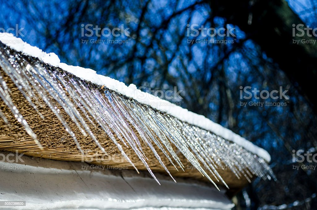 Icicles which are hanging down from a roof stock photo