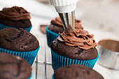 Close up photograph of a delicious vanilla cupcake with chocolate frosting. The cupcake paper is being pulled off and about to be eaten. The photograph is taken from the perspective of the person eating the cupcake. Focus is on the front portion of the cupcake and fades quickly.