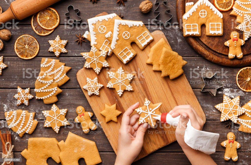Prozess der Weihnachtsbäckerei Sahnehäubchen. Nicht erkennbare Frau hausgemachte Kekse dekorieren - Lizenzfrei Abenddämmerung Stock-Foto