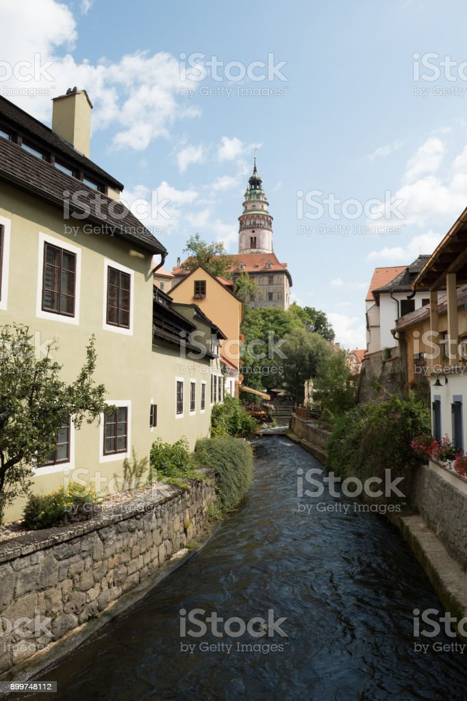 Iconic Castle Tower in Cesky Krumlov, Czech Republic. Renaissance Castle Tower against a blue sky and puffy white clouds. Picturesque town of Cesky Krumlov, houses on both sides of the river. stock photo