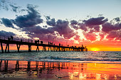 Iconic Glenelg jetty with people silhouettes reflecting in wet sand during colorful dramatic  sunset