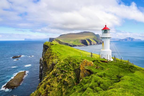 iconische rode en witte vuurtoren op het eiland mykines - faeröer stockfoto's en -beelden
