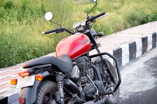 Iconic red motorcycle from royal enfield parked on the side of a street
