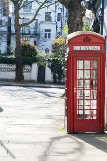 London - March 30: Iconic red phone booth in front of white town houses in Kensington on March 30, 2017. stock photo