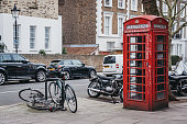 London, UK - February 16, 2019: Iconic red telephone boxes in Primrose Hill, London. Red phone boxes can be found in current or former British colonies around the world.