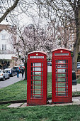 London, UK - March 2, 2019: Iconic red telephone boxes in Hampstead, London. Red phone boxes can be found in current or former British colonies around the world.