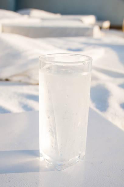ahşap masaya gölge düşüren su damlaları ile buzlu soğuk bardak su - salud stok fotoğraflar ve resimler