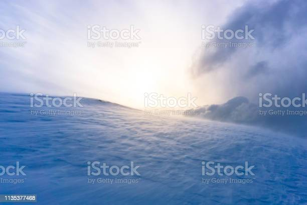Photo of icy landscape during a snowstorm at sunset in Tromsø, Norway