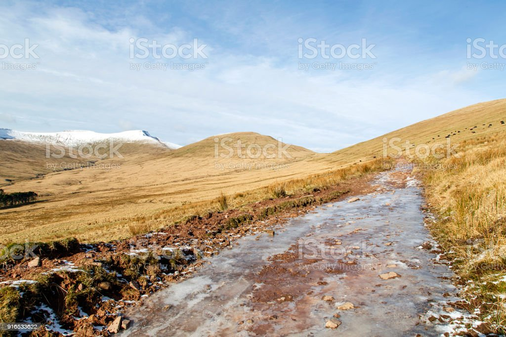 Icy path to Pen y Fan mountain in the Brecon Beacons National Park with winter snow on the Taf Trail. stock photo
