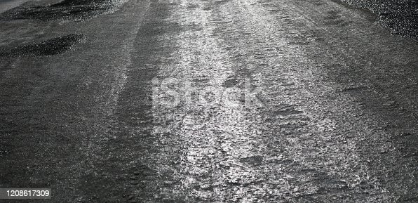 833130962 istock photo Icy road. Selective focus. Hazard concept ice-crusted ground. Black and white image. 1208617309